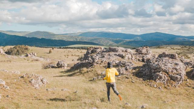 Un homme courant au milieu d'un chaos rocheux.